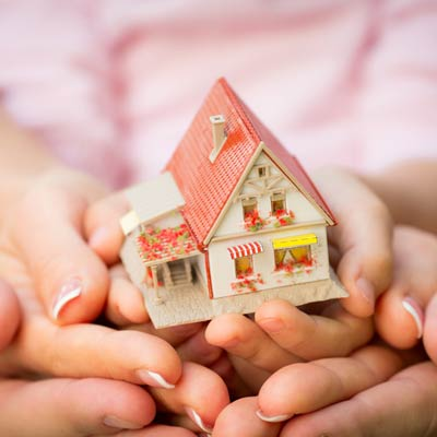 family hands holding model home