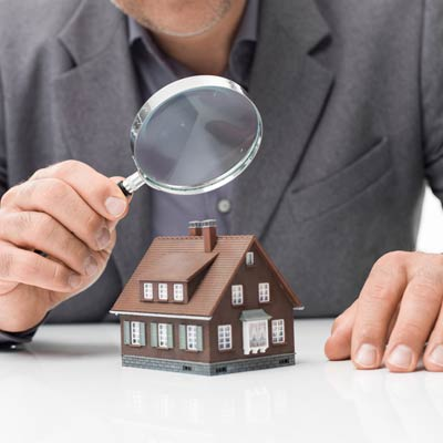 man holding magnifying glass over model home